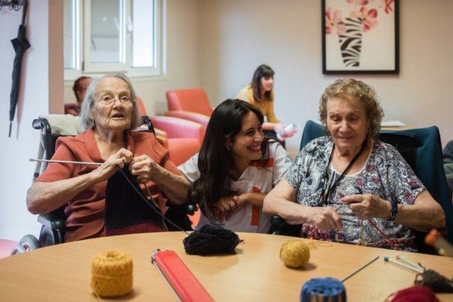 KORIAN Pressebild: Lächelnde Pflegerin mit glücklichen Senioren in einem Aufenthaltsraum in einem Pflegeheim