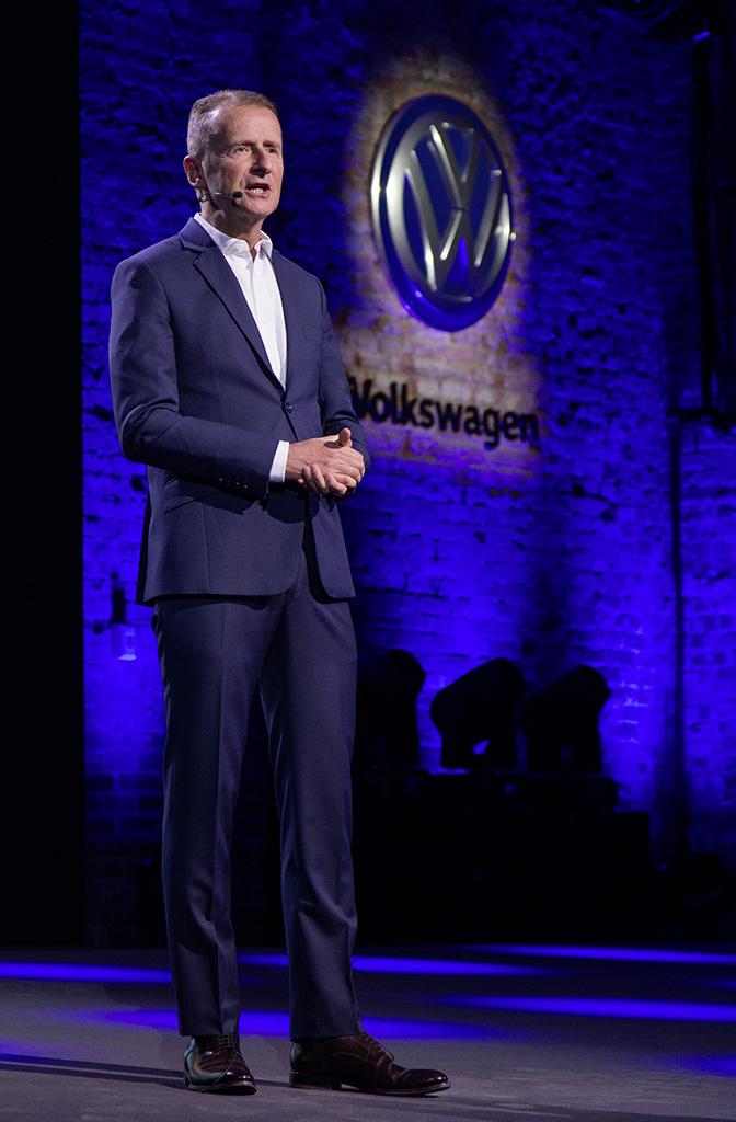 Dr. Herbert Diess vor VW-Logo